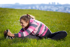 Young Beautiful Woman Stretching her Leg in the City Park. Young Beautiful Woman Doing Exercises on the Grass in the City Park Royalty Free Stock Photo