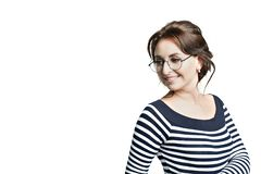 A young beautiful woman in a striped tight blouse and in round glasses widely smiles white teeth. Looks to the left. Isolated on white background stock images