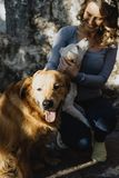Young beautiful woman stroking two dogs and smiling Stock Photo