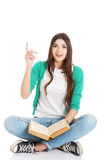 Young beautiful woman student sitting with book an Stock Photography