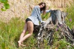Young beautiful woman on stump Royalty Free Stock Photo