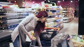 Young beautiful woman with stunning earings and red hair is laying out products on a checkout count in a grocery store.