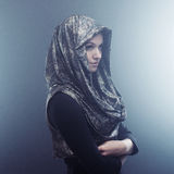 Young beautiful woman in stylish Cape with hood. Portrait on dark background, smoke and fog Stock Photography