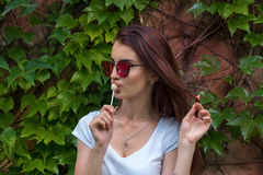 Young beautiful woman sucking a lollipop at the park Stock Photo
