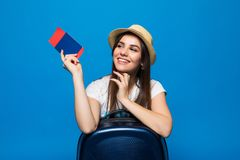 Young beautiful woman with suitcase holding passport on blue background Stock Photo