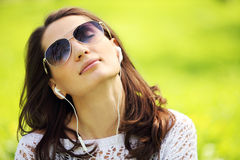 Young beautiful woman in summer park enjoy music Stock Photography