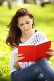 Young beautiful woman in summer park reading a book Stock Images