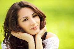 Young beautiful woman in summer park smiling Royalty Free Stock Photography
