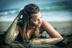 A young and beautiful woman on the beach. A young and beautiful woman in summer posing on the shore of the sea covered with sand Royalty Free Stock Photo