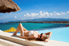 Young beautiful woman sunbathing. Nice sea view. Stock Photo