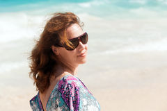 Young beautiful woman in sunglasses on a beach. Young beautiful Caucasian woman in sunglasses. Summer outdoor portrait on the sea coast Royalty Free Stock Photos
