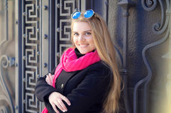 Young beautiful woman in sunglasses. Portrait of a beautiful young woman, long-haired blonde. she wears a black coat, a bright pink scarf. color sunglasses with Royalty Free Stock Images
