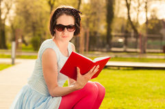 Young beautiful woman with sunglasses reading a book outdoor Royalty Free Stock Photography