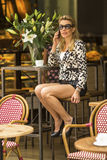 Young beautiful  woman in sunglasses sitting in a cafe talking on a cell phone. Stock Photo