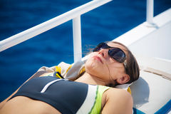 Young beautiful woman in sunglasses sunbathing in upper deck in Stock Image