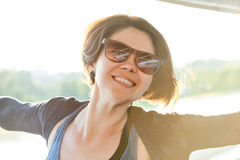 Young beautiful woman in sunglasses at sunset Stock Photos