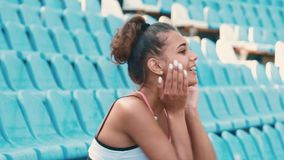 Side view of beautiful young woman sitting on tribunes at sports stadium. Young beautiful woman in sunny weather at the stadium. Sits alone on blue seats stock video footage