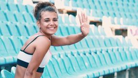 Side view of beautiful young woman sitting on tribunes at sports stadium. Young beautiful woman in sunny weather at the stadium. Sits alone on blue seats stock footage
