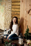 Young beautiful woman in sweater and blue jeans sitting on floor at home Stock Photo
