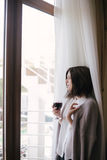 Young beautiful woman in a sweater drinking red wine near big window Royalty Free Stock Images