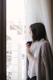 Young beautiful woman in a sweater drinking red wine near big window Royalty Free Stock Photos