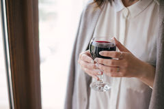 Young beautiful woman in a sweater drinking red wine near big window Stock Photos