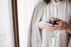 Young beautiful woman in a sweater drinking red wine near big window Stock Images