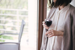 Young beautiful woman in a sweater drinking red wine near big window Stock Photo