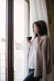 Young beautiful woman in a sweater drinking red wine near big window Stock Photography