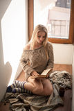 Young beautiful woman in a sweater reading a book. Young beautiful woman in a sweater reading a book near the window Royalty Free Stock Photos