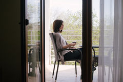 Young beautiful woman in a sweater sitting on a cozy terrace with a glass of red wine Royalty Free Stock Image