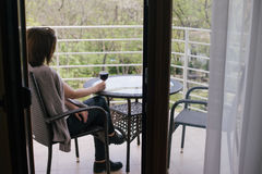 Young beautiful woman in a sweater sitting on a cozy terrace with a glass of red wine Royalty Free Stock Images
