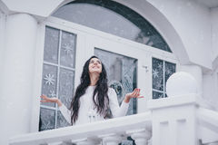 Young beautiful woman in sweater standing under the snowfall Stock Image