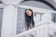 Young beautiful woman in sweater standing under the snowfall Royalty Free Stock Photos