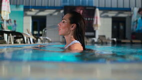 Young beautiful woman swimming in the blue pool stock footage