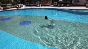 Young beautiful woman swimming on a blue pool water stock video