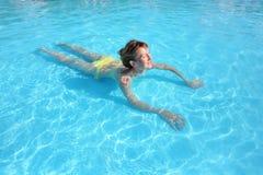 Young beautiful woman swimming in paddling pool stock photo