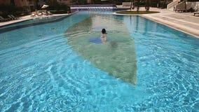 Young beautiful woman swimming on swimming pool stock footage