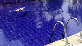 Young beautiful woman swims in pool. The young beautiful woman swims in pool stock video footage