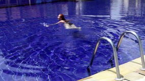 Young beautiful woman swims in pool. The young beautiful woman swims in pool stock footage