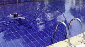 Young beautiful woman swims in pool. The young beautiful woman swims in pool stock video