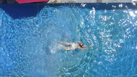 The young beautiful woman swims in the pool in a tropical garden,Aerial view from drone. The young beautiful woman swims in the pool in a tropical garden stock footage