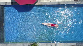 The young beautiful woman swims in the pool in a tropical garden,Aerial view from drone stock video