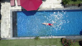 The young beautiful woman swims in the pool in a tropical garden,Aerial view from drone stock video footage
