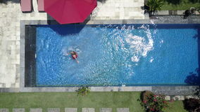 The young beautiful woman swims in the pool in a tropical garden,Aerial view from drone. The young beautiful woman swims in the pool in a tropical garden stock video footage