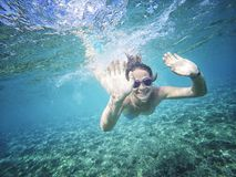 Beautiful woman swims underwater, smiling and waves a hand. Young beautiful woman swims underwater, smiling and waves a hand stock image