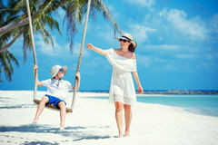Young beautiful woman swinging son on a tropical beach, Koh Phangan island. Thailand. Stock Photo