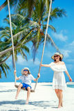 Young beautiful woman swinging son on a tropical beach, Koh Phangan island. Thailand. Stock Photography