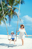 Young beautiful woman swinging son on a tropical beach, Koh Phangan island. Thailand. Stock Image