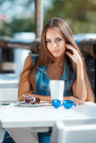 Young beautiful woman at a table in summer cafe Royalty Free Stock Images